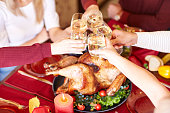Close-up family clinking glasses on Thanksgiving on a table background. Cheers with champagne. Celebration concept.
