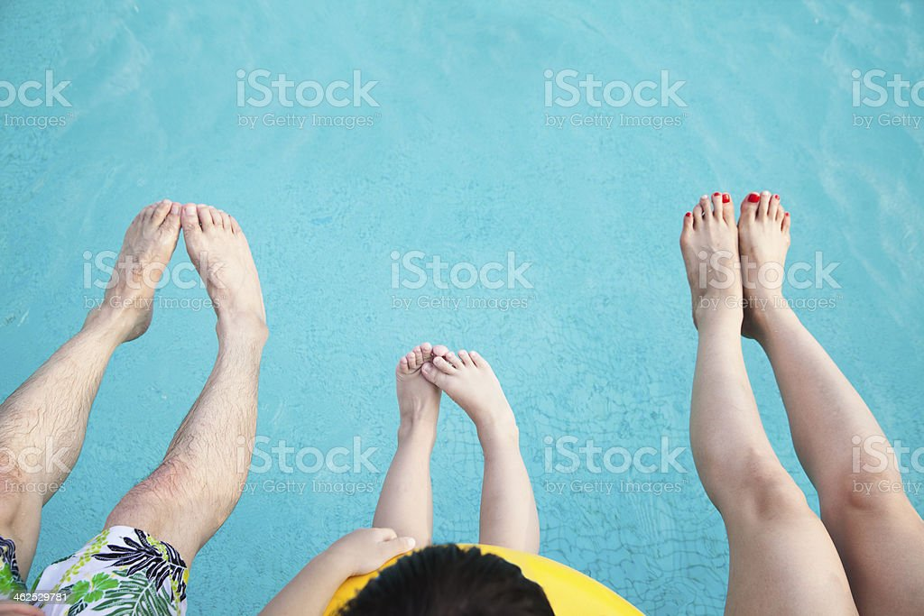Close-up feet on young family in the pool stock photo