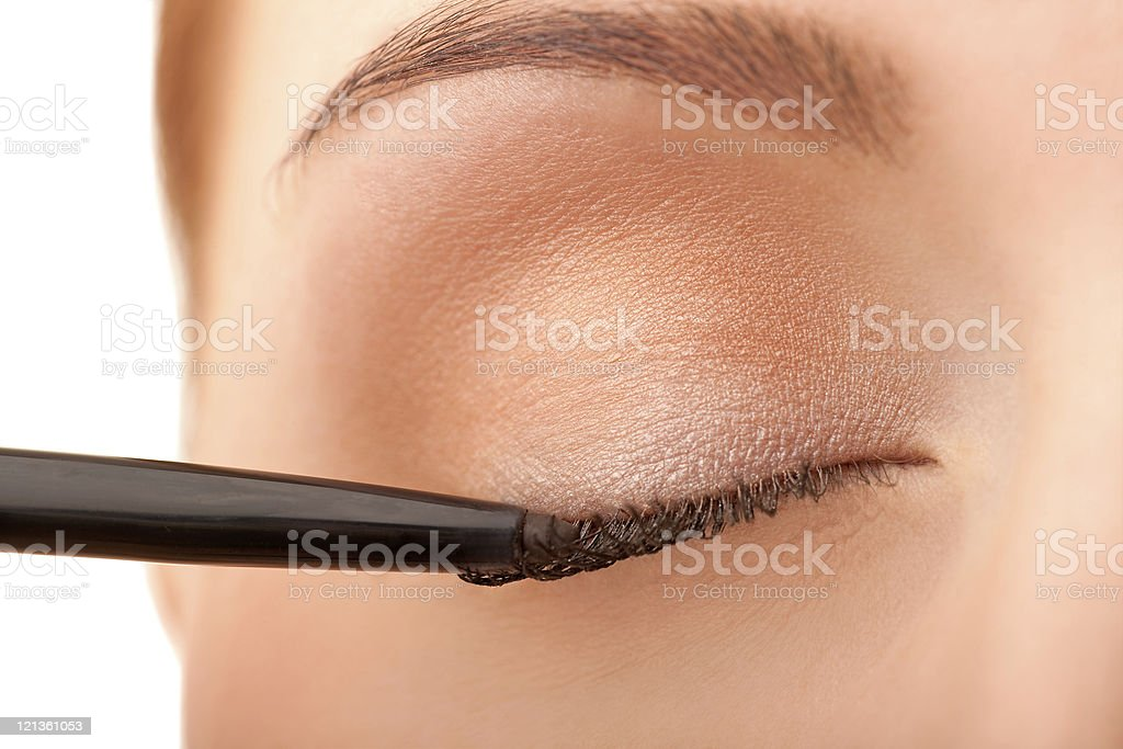 Close-up female applying eye liner stock photo