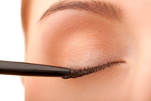 Close-up female applying eye liner stock photo