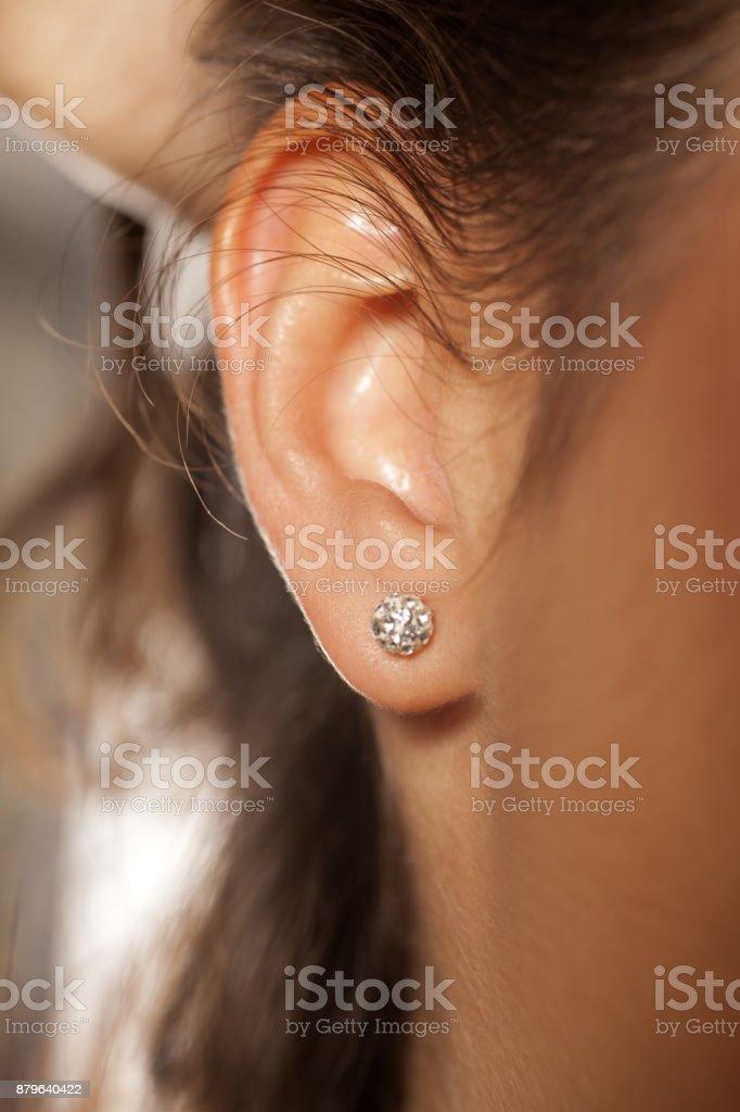 Closeup de ouvido feminino com um pequeno brinco luxuoso - foto de acervo