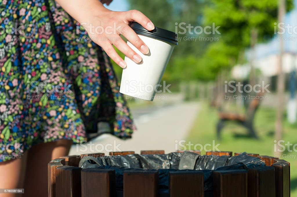 Close-up female hand throwing paper cup on trash stock photo