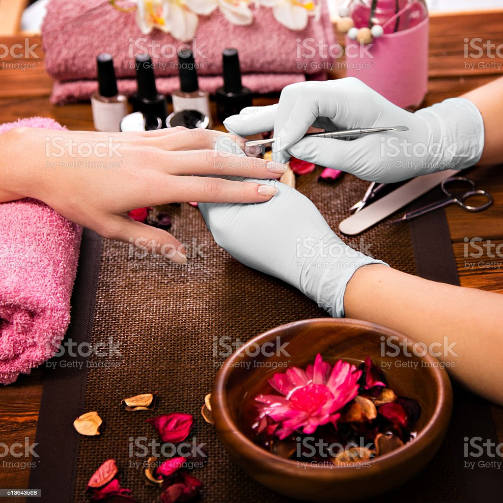 Closeup finger nail care by manicure specialist in beauty salon....