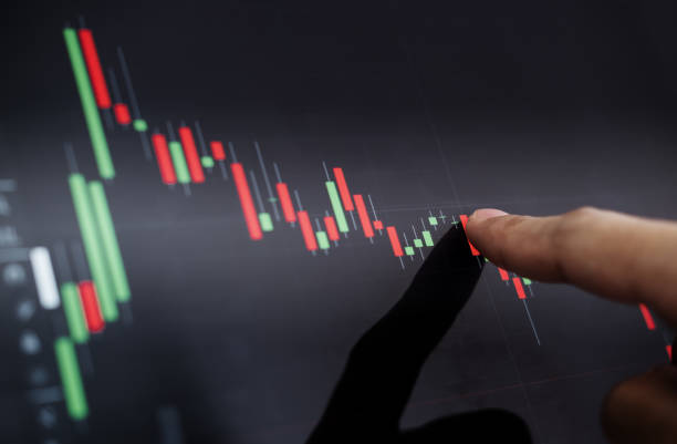 close-up finger pointing on stock exchange chart - human finger stock pictures, royalty-free photos & images