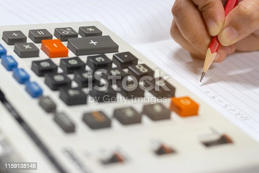 Close-up fingers holding pencil are writing and using calculator to calculate the Mathematics on wooden table. Finances business savings and accounting concept or Education idea.