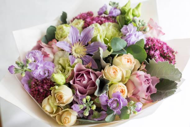 close-up florale komposition mit rosen und mischung blumen auf hellem hintergrund. - pfingstrosen pflege stock-fotos und bilder