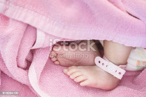Closeup foot of baby with newborn ankle tag on bed in hospital textured background