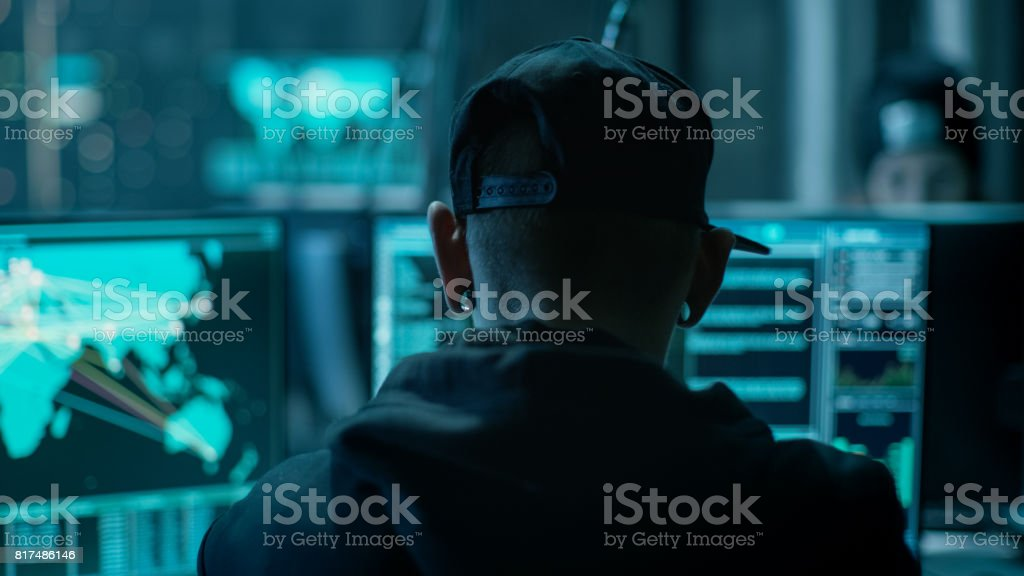 Close-up Frame from the Back of Working Hacker Organizing Advanced Virus Attack on Corporate Servers. Place is Dark and Has Multiple displays. stock photo