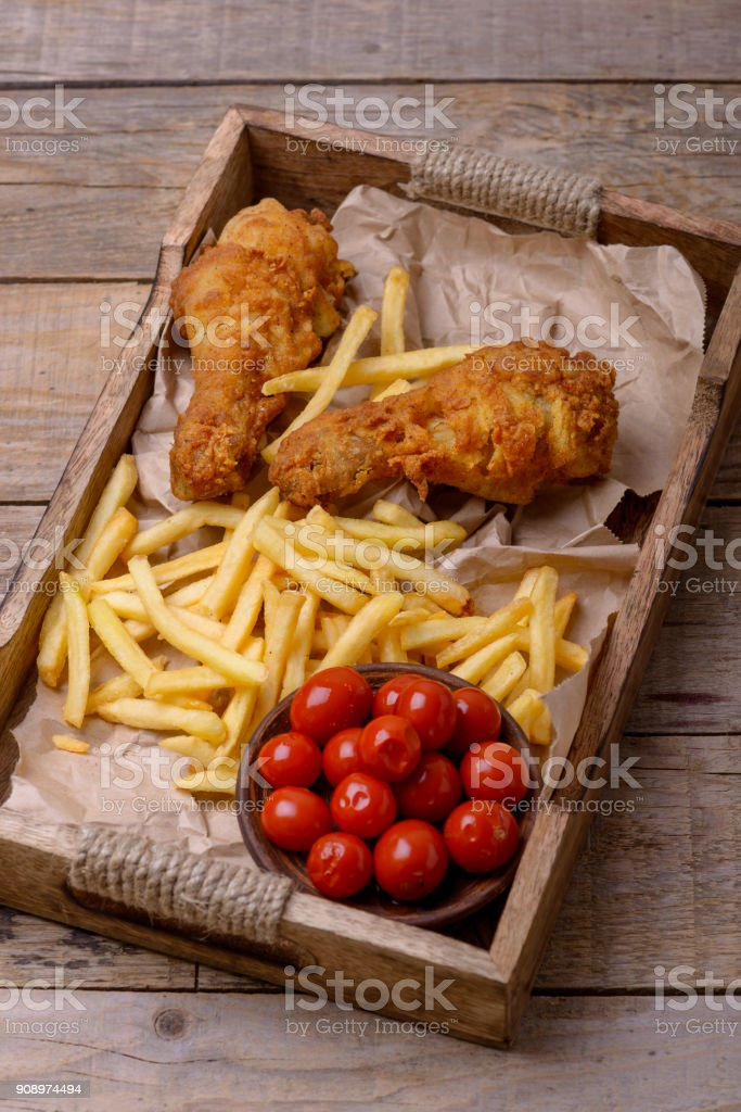 Closeup fried chicken legs and french fries with marinated tomatoes stock photo