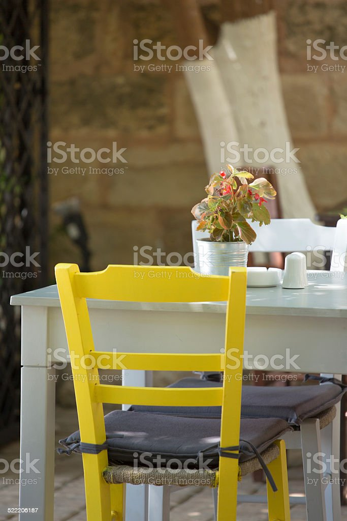 Close-up from a Yellow chair and white table. stock photo