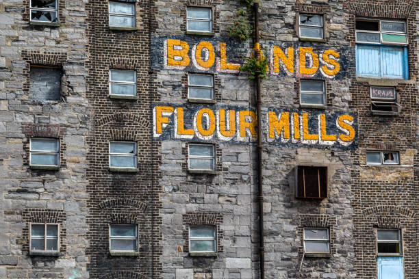 Closeup front facade view of the old abandoned in decay factory mill with company name. stock photo