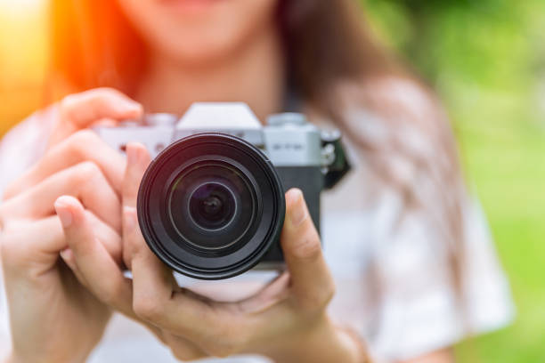 closeup front lens of mirrorless camera in woman teen photographer - macchina fotografica foto e immagini stock