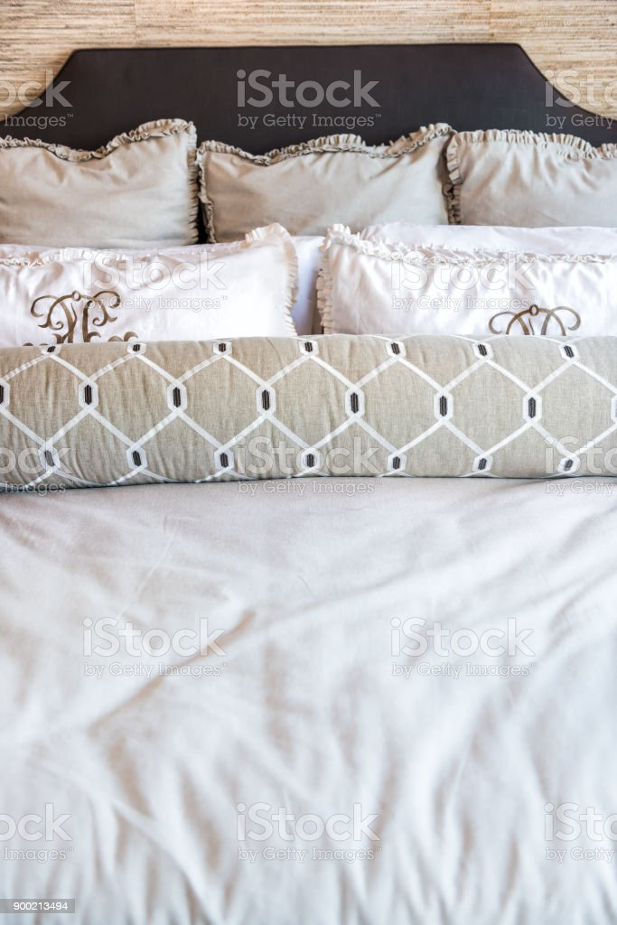 Closeup front view of new bed comforter with decorative pillows in bedroom in staging model home apartment or house stock photo