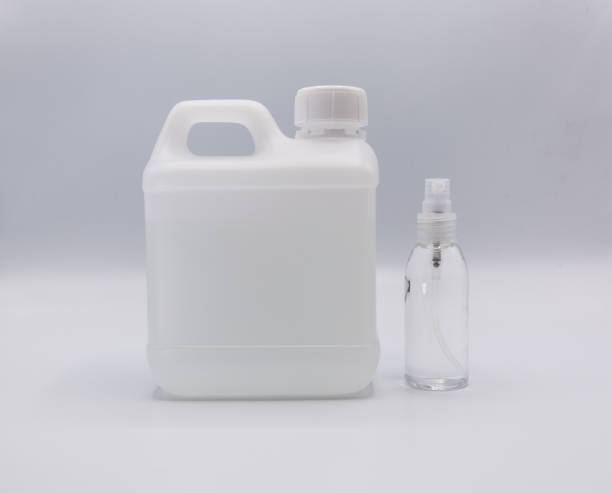 Closeup gallon bottle of clear alcohol refill and hand spray isolated on white background Closeup gallon bottle of clear alcohol refill and hand spray isolated on white background - coronavirus and covid-19 prevention concept gallon stock pictures, royalty-free photos & images