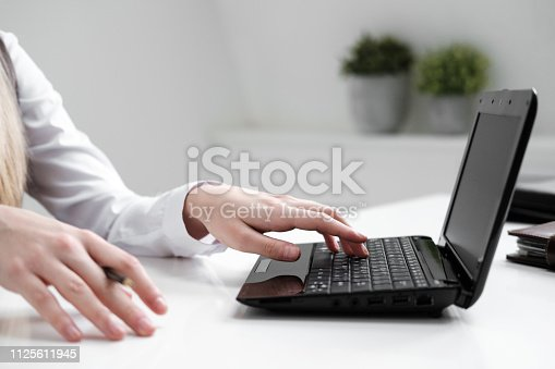 Close-up, girl's hands on the background of the white table, typing on a laptop. Light white office, work.