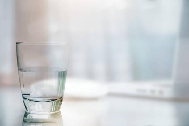 Primer plano de agua limpia sobre la mesa blanca con imagen borrosa del fondo del ordenador portátil y del ratón. - foto de stock