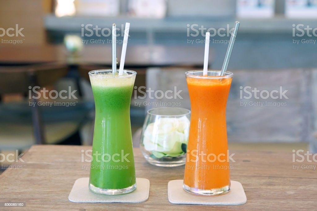 Closeup glass of cold pressed juice on wooden table, Fresh mixed fruits made from carrot, passion, fruit, cantaloupe, wolfberry, gotu kola,curcuma, guava and pineapple. stock photo