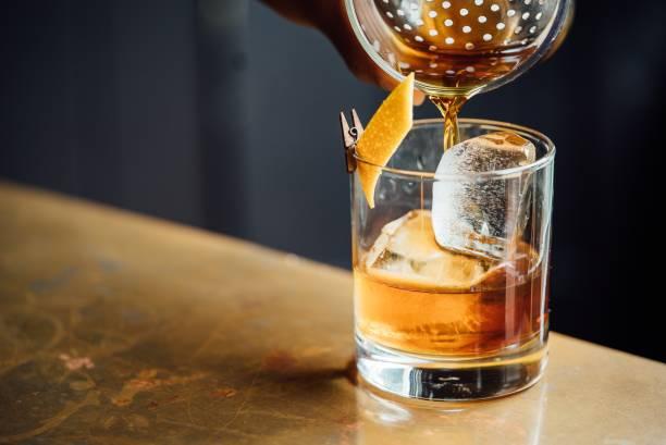крупным планом стекла с алкоголем в коктейль-баре - напиток стоковые фото и изображения
