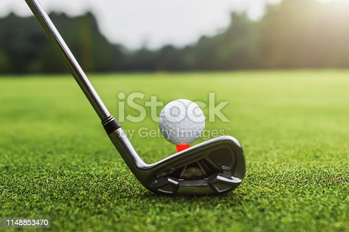 istock closeup golf club and golf ball on green grass wiht sunset 1148853470