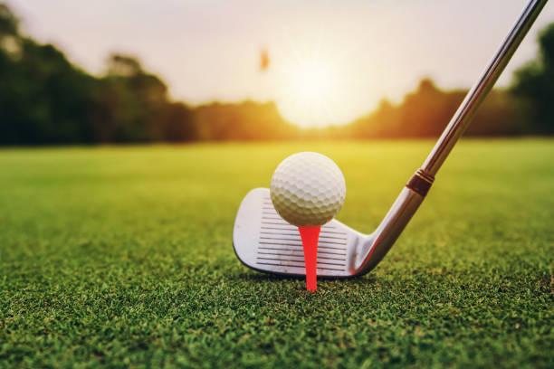Golfclub und Golfball auf grünem Gras bei Sonnenuntergang – Foto