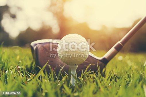 istock closeup golf club and golf ball on green grass wiht sunset 1164735755