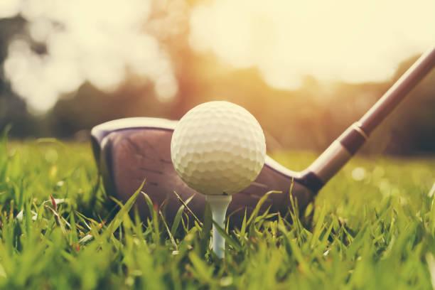 nahaufnahme golfclub und golfball auf grünem rasen mit sonnenuntergang - golf stock-fotos und bilder