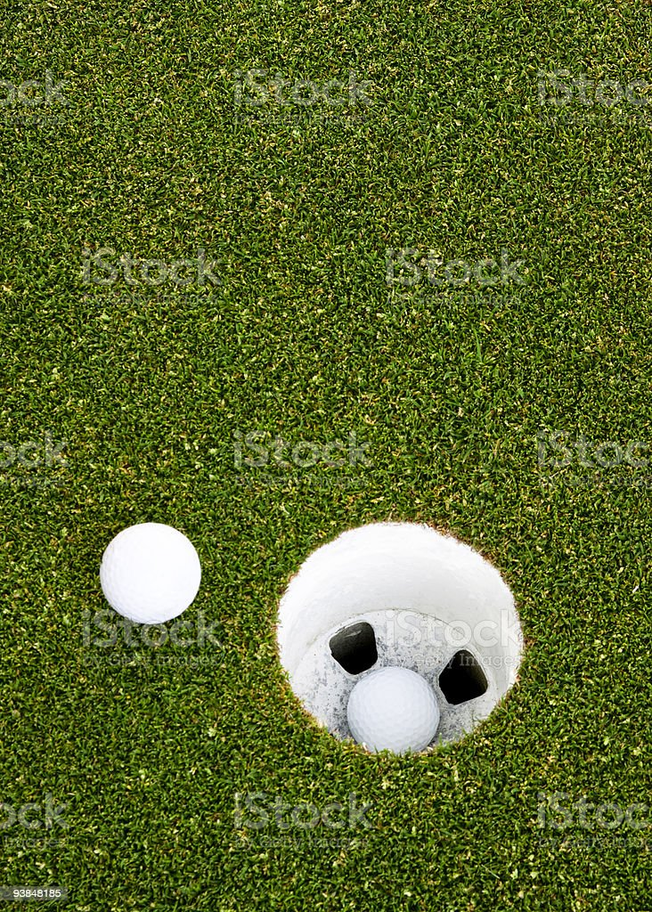 Closeup golfball inside the hole and one golfball near hole royalty-free stock photo