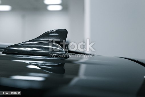881639308istockphoto Close-up GPS antenna shark fin shape on a roof of car for radio navigation system. Antenna shark fin on blurry background. Car detail 1146630408