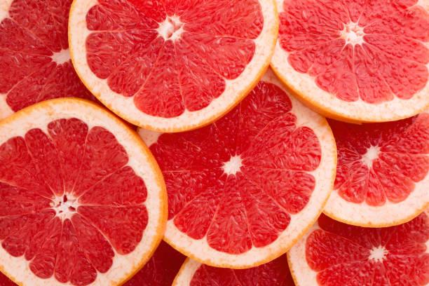 Close-up Grapefruit Scheiben abstrakten Hintergrund in lebenden Korallen Farbe. – Foto