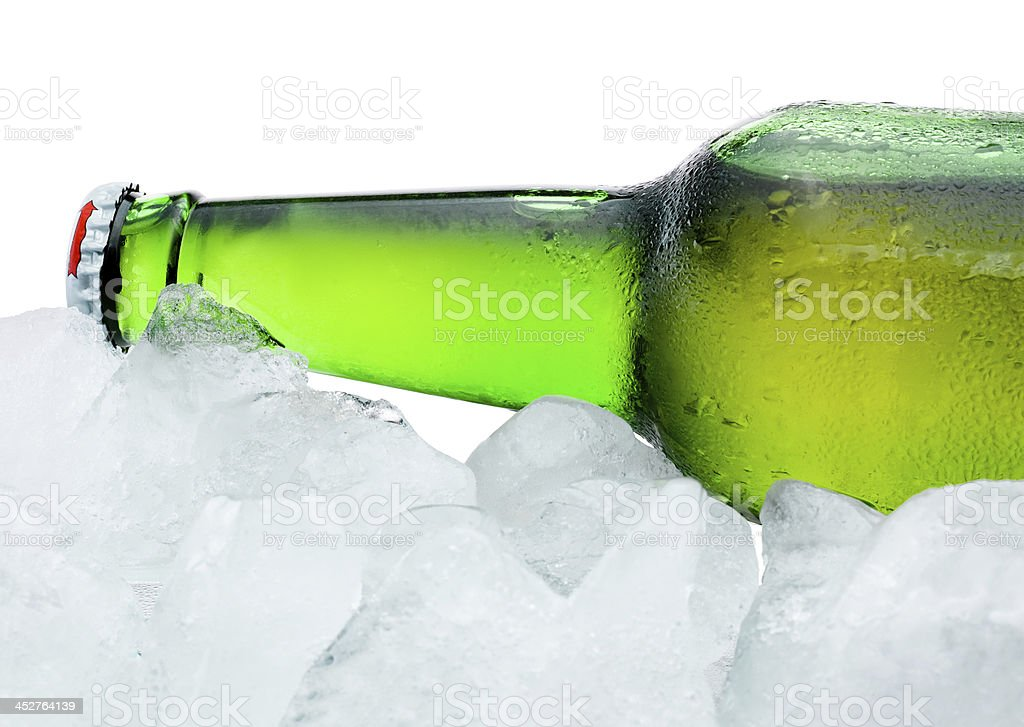 Close-up Green Beer Bottle with Condensation cool in ice isolated royalty-free stock photo