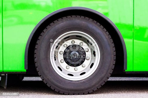 Closeup green bus wheel, full frame horizontal composition with copy space