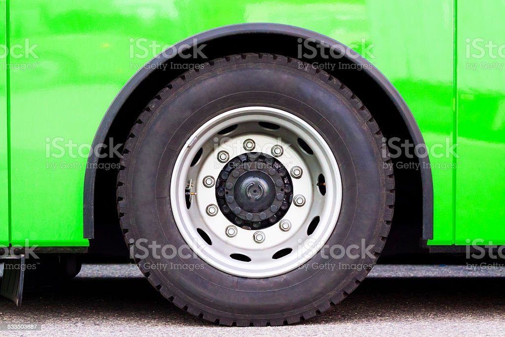 Closeup green bus wheel, full frame horizontal composition stock photo
