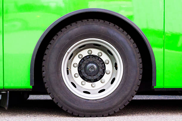 Closeup green bus wheel, full frame horizontal composition Closeup green bus wheel, full frame horizontal composition with copy space wheel stock pictures, royalty-free photos & images