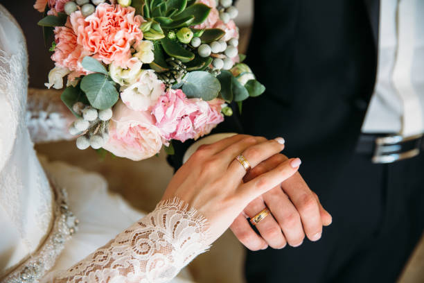 closeup groom and bride are holding hands at wedding day ang show rings. concept of love family - помолвка стоковые фото и изображения