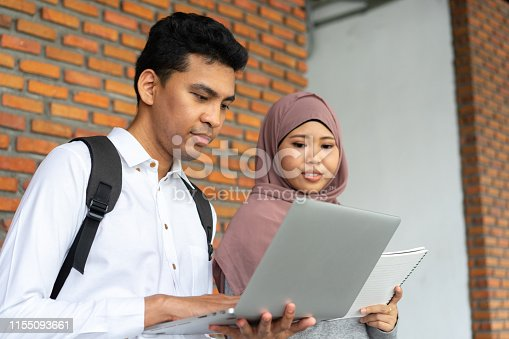 istock closeup group of asian muslim young student man and man using laptop and writing on notebook after help together for research knowledge information at library university , study abroad lifestyle education concept 1155093661