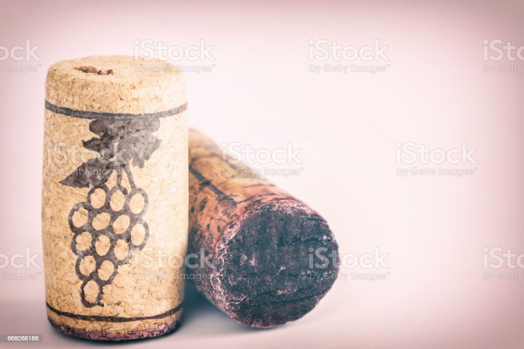Close-up group of two old wine corks bottle stopper in studio on pink background cross-processed - Photo