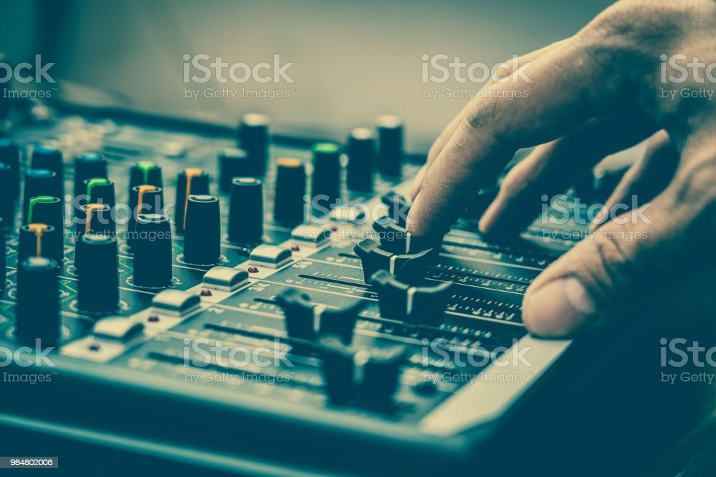 Closeup hand adjust the audio mixer, music equipment concept stock photo