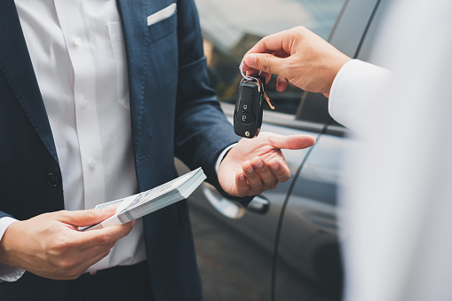 Closeup hand giving a car key and money for loan credit financial, lease and rental concept