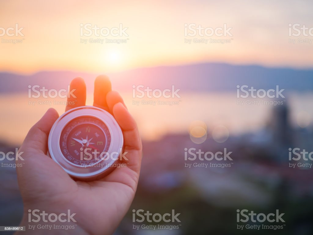 Closeup hand holding compass with  mountain and sunset sky background. stock photo