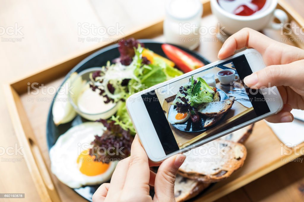 closeup hand holding phone shooting food photograph stock photo
