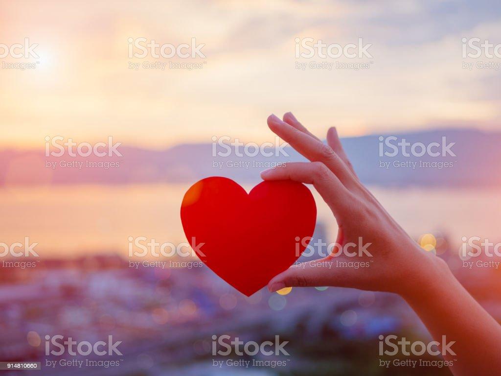 Closeup Hand mit roten Herzen während Sonnenuntergang Hintergrund. Happy, Liebe, Valentinstag Idee, Konzept, Symbol, Zeichen. – Foto