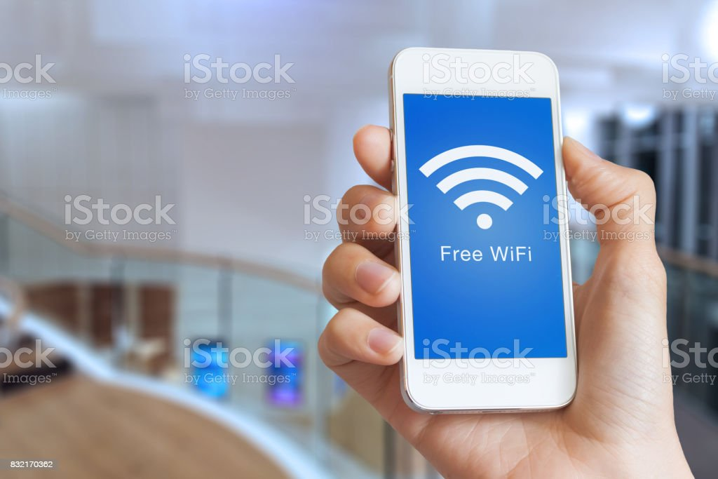 Closeup hand holding smartphone with free WiFi hotspot on screen stock photo