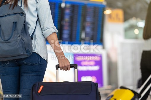 842907838 istock photo Closeup hand holding the luggage over the flight board for check-in at the flight information screen in modern an airport, travel and transportation concept 1057490274