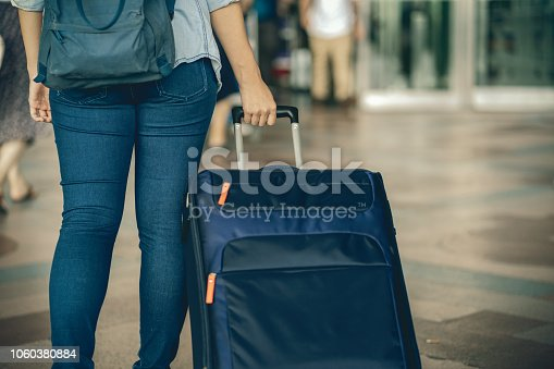 842907838 istock photo Closeup hand holding the luggage over the flight board for check-in at the flight information screen in modern an airport, travel and transportation concept 1060380884