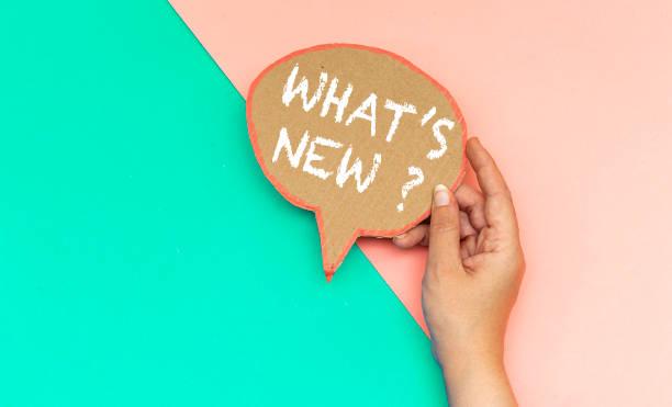 closeup hand holding what's new ? speech bubble - new imagens e fotografias de stock