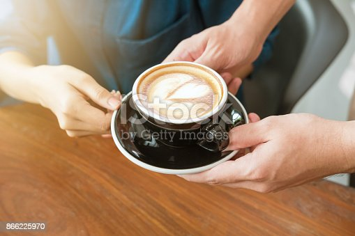istock Close-up hand of a waitress serving a cup of coffee to customer. Selective focus. 866225970