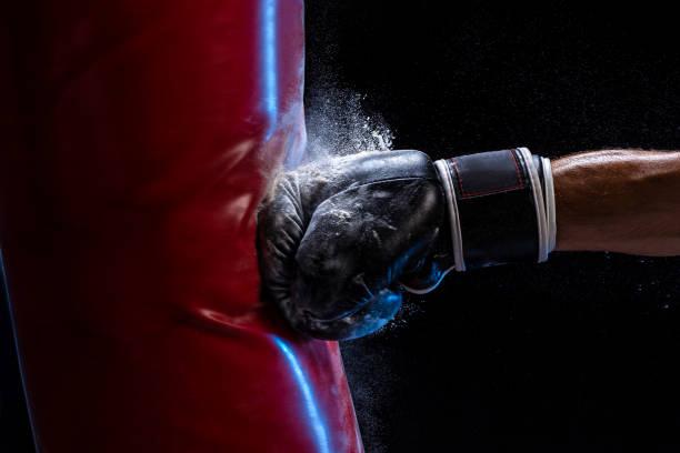 Mano de primer plano del boxeador en el momento del impacto en el bolso de perforación sobre fondo negro - foto de stock