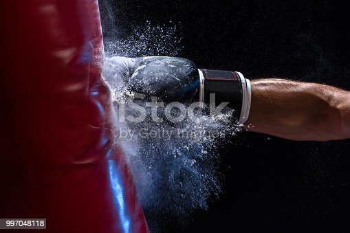 istock Close-up hand of boxer at the moment of impact on punching bag over black background 997048118
