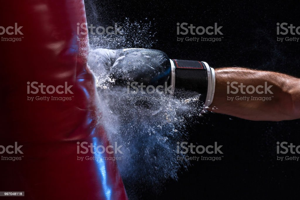 Close-up hand of boxer at the moment of impact on punching bag over black background stock photo