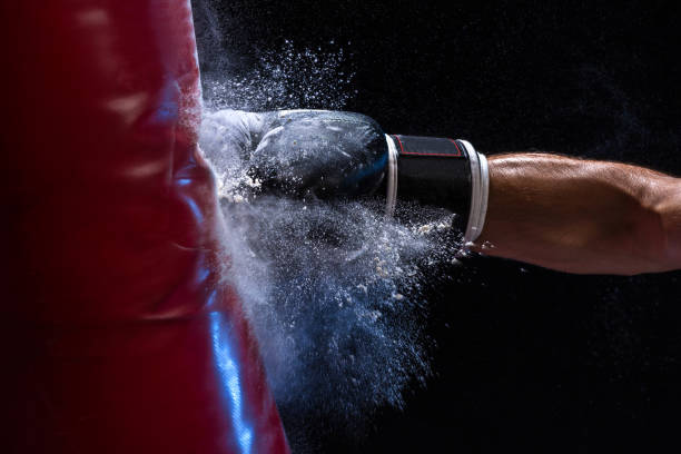 Cтоковое фото Close-up hand of boxer at the moment of impact on punching bag over black background